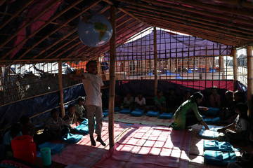 A child jumps to touch the globe while in a learning center at the Jamtoli refugee camp in Cox's Bazar