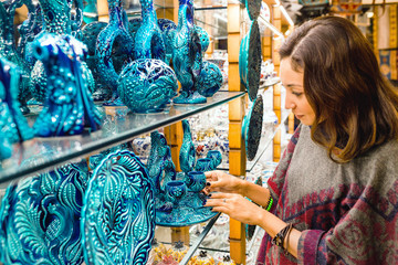 Tourist woman choosing blue ornamental ceramic dishes in souvenir shop