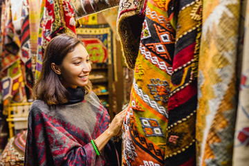 Young Woman Shopping For A New traditional oriental poncho or carpet at tourist market in Cappadocia. Middle east fashion and clothes concept