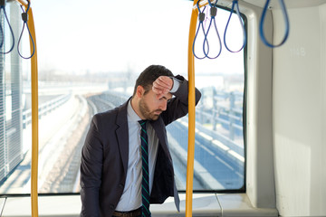 Businessman commuter is traveling and he is sad and tired
