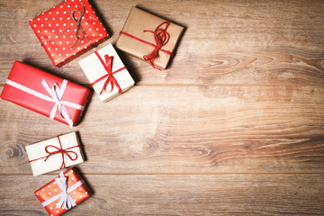 Christmas presents in decorative boxes on wooden background and copy space for text