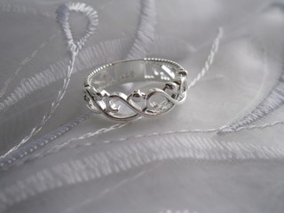 A beautiful female silver engagement ring on a white organza with embroidery