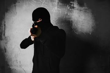 Terrorist shooting with his war gun weapon with grunge room wall background. Criminal and Dangerous illegal people concept. Terrorist and war theme. Dark tone and high contrast use