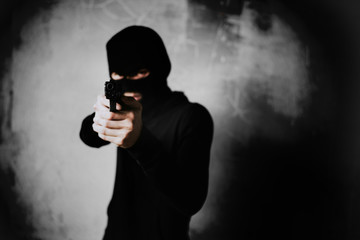 Terrorist shooting with his mini gun weapon with grunge room wall background. Criminal and Dangerous illegal people concept. Terrorist and war theme. Dark tone and high contrast use