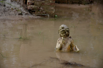 An ancient statue is partly submerged under water at an archaeological site, following flash floods which hit the area, at the village of Dion