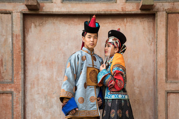 Young Mongolian couple in a traditional 13th century costume in a temple. Ulaanbaatar, Mongolia.