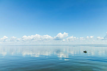 Amazing beautiful blue sky with light white clouds over calm smooth river surface. Summertime. Sunny day.
