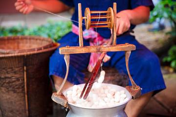Man Unwinding And Reeling Silk Cocoons In Factory