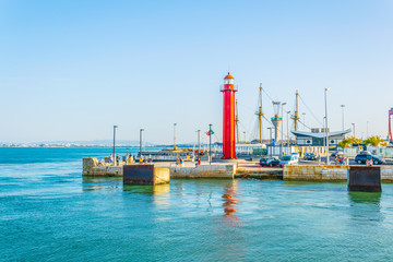 People are strolling on waterfront in Cacilhas in Lisbon, Portugal.