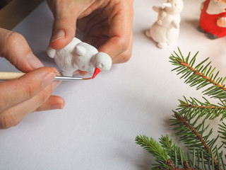 Artist is working in an atelier. Art and small sculpture snowman. Preparing for Christmas.