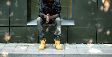 Wall Mural - Street fashion concept, african man in black jacket, jeans and boots sitting in the city