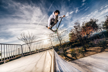 Young man with scooter making a jump on Skatepark during sunset
