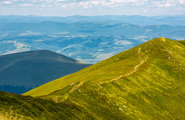 footpath through mountain ridge with grassy slopes. beautiful summer nature scenery