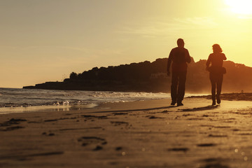 Silhouette of couple walking on the beach at sunset