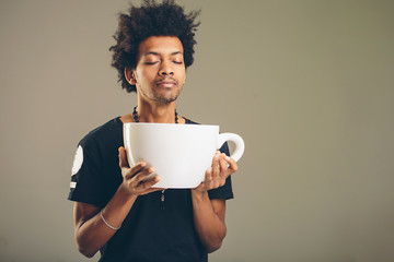 man holding funny huge and oversized cup of black coffee Wall mural