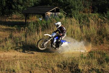 Enduro, motocyklista na motorze crossowym w kałuży.