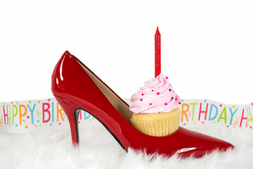 cupcake with candle in red high heel shoe on fur with happy birthday party streamer