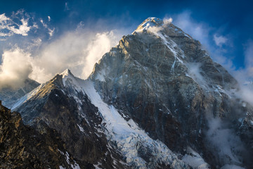 Himalayan summit Pumori against a blue sky with clouds. Everest