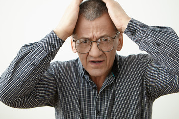 Portrait of stressed desperate senior male in checkered shirt and eyeglasses holding hands on his head, feeling nervous because of problem. Elderly people, stress, negative emotions and reaction