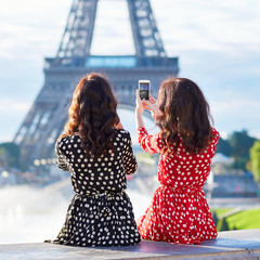 Twin sisters taking selfie near the Eiffel tower in Paris