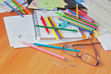 Glasses on the background of colored pencils and paper. The clutter on the desktop.