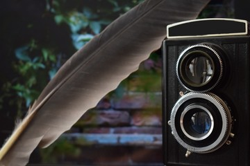 old camera, retro camera, vintage, with a brick wall and a feather in the background