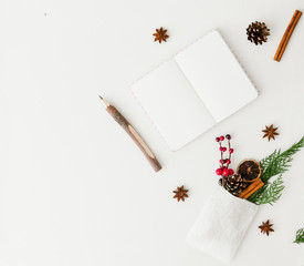 Notebook with Christmas decorations over white background