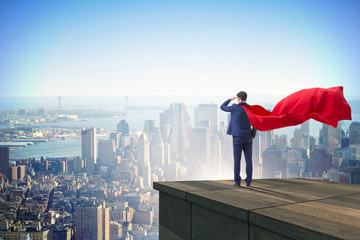 Super hero businessman  on top of building ready for challenge Wall mural