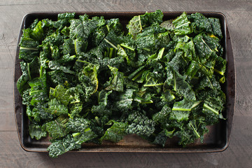 Green kale pieces on stone prepared with olive oil for the oven horizontal shot