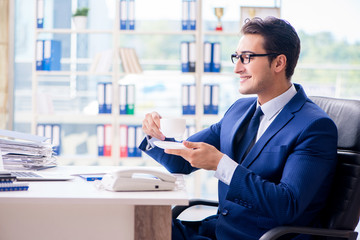 Businessman drinking coffee in the office during break