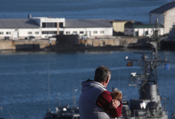 A man holds a dog as he looks at ships at the naval base where the missing at sea ARA San Juan submarine sailed from, in Mar del Plata
