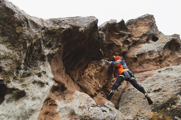 Hipster - climber at the age of climbing up a beautiful rock without insurance and helmet