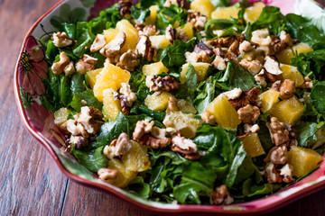 Pineapple Salad with greens on a wooden surface.