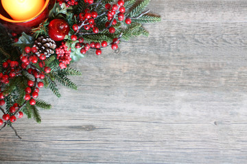 Festive Holiday Christmas Candle with Pine Tree Branches and Berries in Top Corner Over Rustic Wood Background