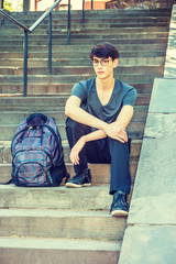 Asian American college student studying in New York. 20 years old man wearing v neck T shirt, black pants, sneakers, sunglasses, sits on stairs on campus, bag beside him. Filtered look with soft light