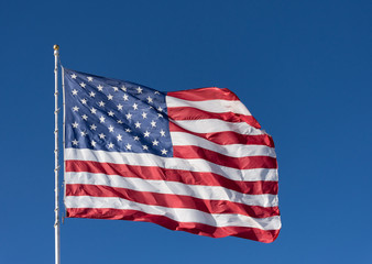 The stars and stripes of the American flag against a dark blue sky. The flag is unfurled by the wind.
