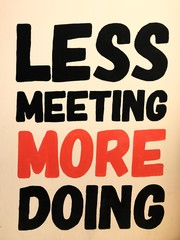 Less meeting more doing words on wall, text quote on wall background in business room.