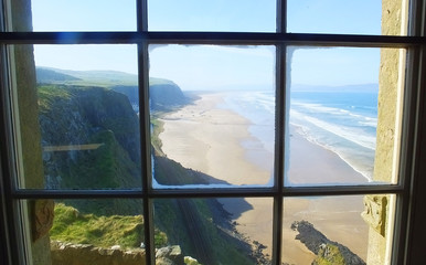 Looking out of window unto benone beach Mussenden Temple blue sky background for text copy Co Derry Londonderry Northern Ireland
