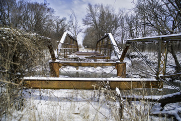 A long abandoned bridge rusts under the winter sky and dreary sky