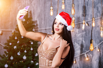 Christmas portrait of beautiful girl. Sexy woman in evening dress wearing santa claus hat. Girl smiling and making selfie on mobile phone