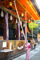 Tourist woman in Yukata Kimono Dress Praying by ringing the golden bell