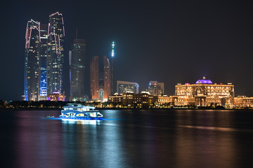 Abu Dhabi buildings skyline from the sea at night