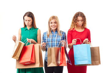 Portrait of three young girlfriends holding bunches of multi-colored shopping bags