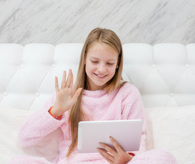 Teen girl using tablet pc on the bed