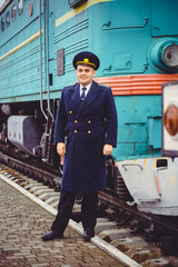 European or American train conductor is on his duty on a platform and other trains. Railway, steam trains, vintage trains