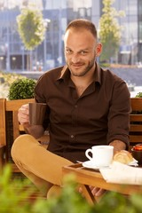 Handsome man drinking coffee outdoors