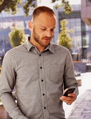 Casual man using mobile outdoors