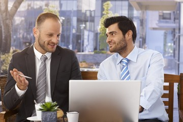 Businessmen discussing ideas on laptop computer