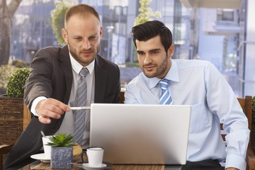 Businessmen working on laptop at outdoor cafe