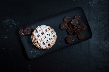 American Pie with cookies . On a black plate